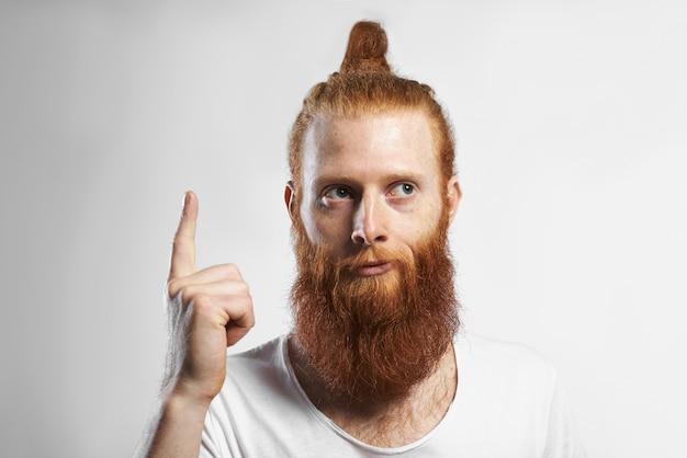 Imagens horizontais de emocional engraçado jovem com barba por fazer com penteado na moda e barba por fazer, tendo uma boa ideia, levantando o dedo e olhando para longe com um sorriso misterioso pensativo. linguagem corporal Foto gratuita