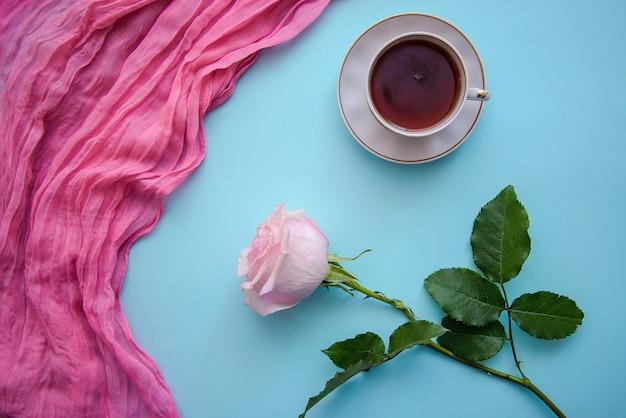Imagens românticas de chá, rosa e tecido rosa sobre fundo azul Foto Premium