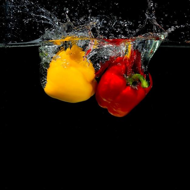 Impacto, de, pimentão pimenta, em, água, ligado, experiência preta Foto gratuita