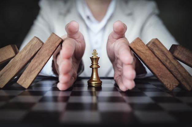 Impedindo o risco de jogar xadrez em um quadro de negócios, conceito de seguro comercial. Foto Premium