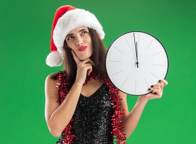 Impressionado olhando para uma bela jovem usando chapéu de natal com guirlanda no pescoço segurando um relógio de parede colocando o dedo na bochecha isolado no fundo verde Foto gratuita