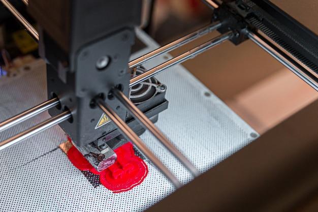 Impressora 3d moderna, imprimindo pequena figura vermelha, closeup vista de cima Foto Premium