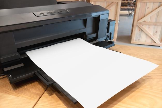 Impressora de papel digital e modelo em branco na mesa de madeira. Foto Premium