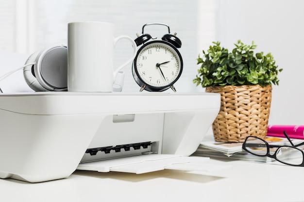 Impressora doméstica branca e fones de ouvido brancos na mesa de escritório Foto Premium
