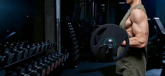 Incógnito homem construção de bíceps com barra. Foto gratuita