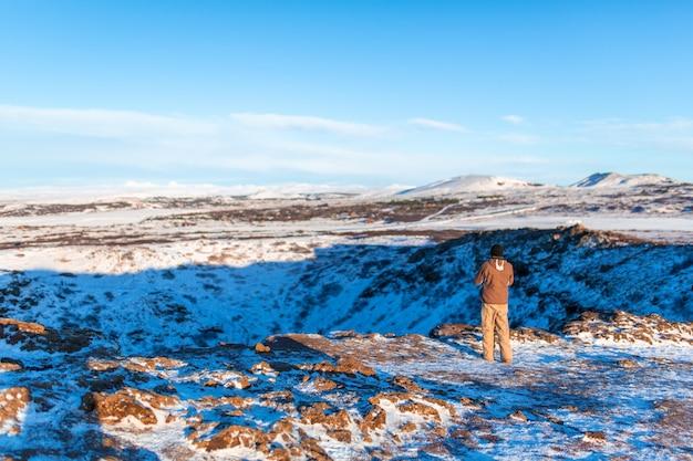 Incrível paisagem de inverno perto do lago kerid. o cara caminha perto da cratera do vulcão kerid no inverno. Foto Premium