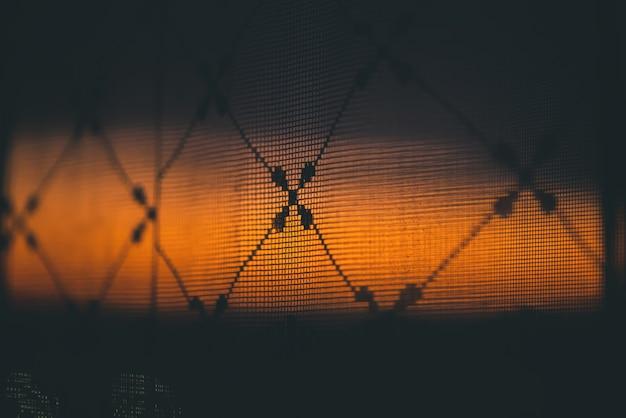 Incrível por do sol vívido romântico na janela atrás de silhuetas de textura de tule. Foto Premium