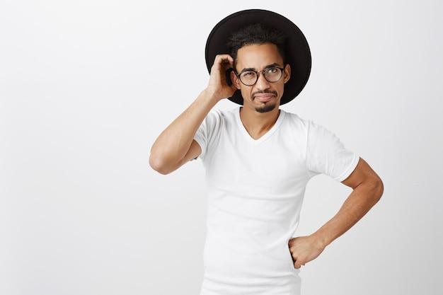 Indeciso e bonito homem afro-americano de óculos e chapéu coçar a cabeça perplexo, parecendo confuso Foto gratuita