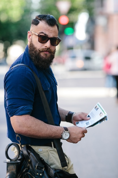 Indivíduo à moda segurando uma brochura Foto gratuita