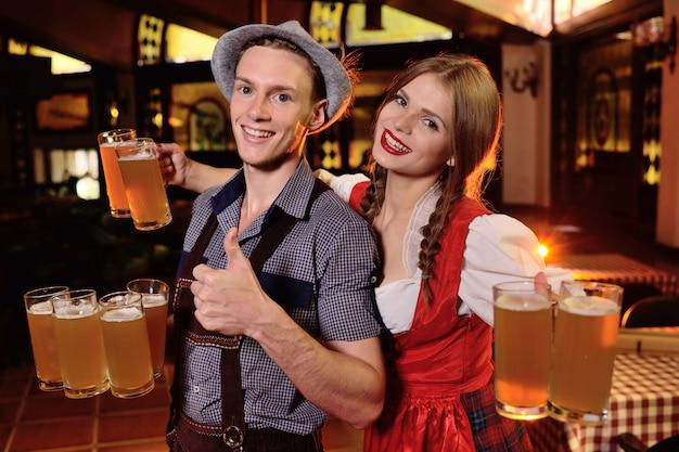 Indivíduo e uma menina na roupa bávara que guarda muitas canecas com cerveja no fundo do bar durante a celebração de oktoberfest. Foto Premium