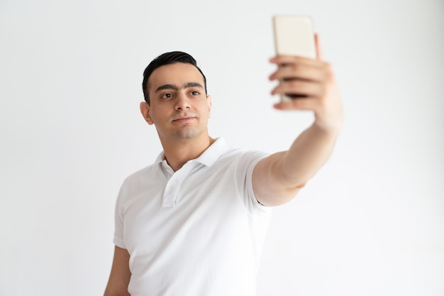 Indivíduo novo de sorriso que toma a foto do selfie no smartphone. homem indiano usando dispositivo digital. Foto gratuita