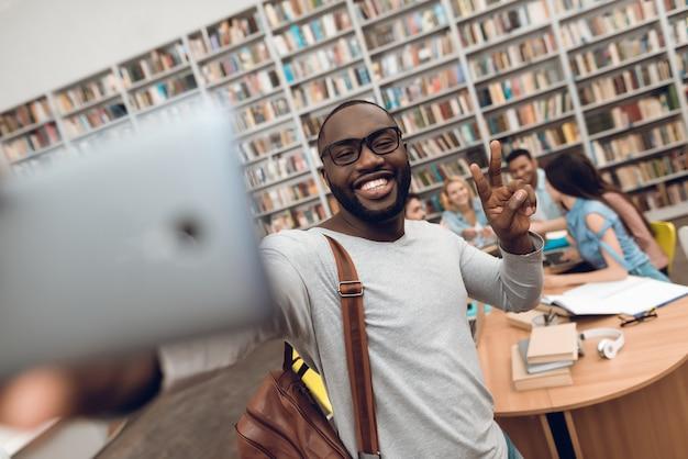 Indivíduo preto que toma o selfie no telefone na biblioteca escolar. Foto Premium