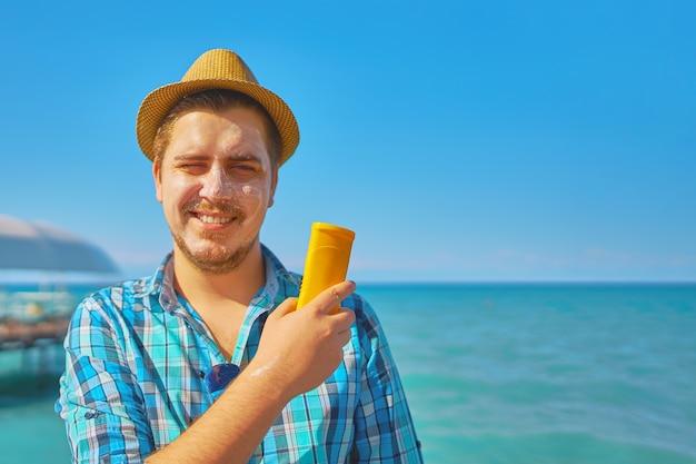 Indivíduo que põe sobre o creme da proteção do sol na cara. Foto Premium