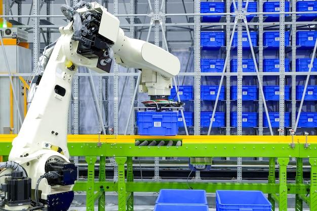 Industrial robótico emocionante azul recipiente de caixa de plástico colocar na esteira no armazém da fábrica inteligente Foto Premium