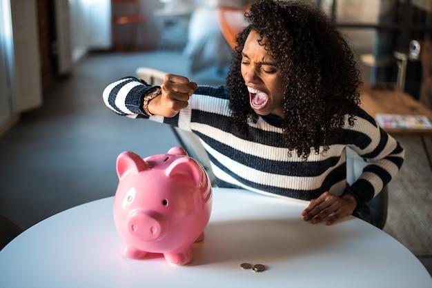Infeliz mulher negra com raiva no cofrinho Foto Premium
