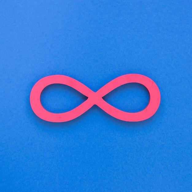 Infinito símbolo rosa sobre fundo azul Foto gratuita