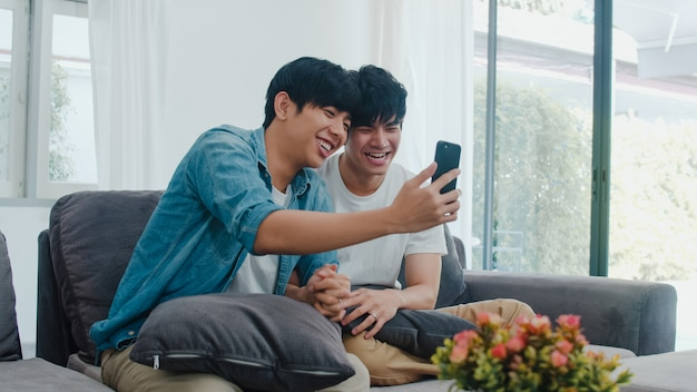 Influenciador asiático casal gay vlog em casa. os homens asiáticos lgbtq felizes relaxam o divertimento usando o upload do vídeo do vlog do estilo de vida do registro do telefone móvel da tecnologia nas mídias sociais ao encontrar o sofá na sala de estar. Foto gratuita
