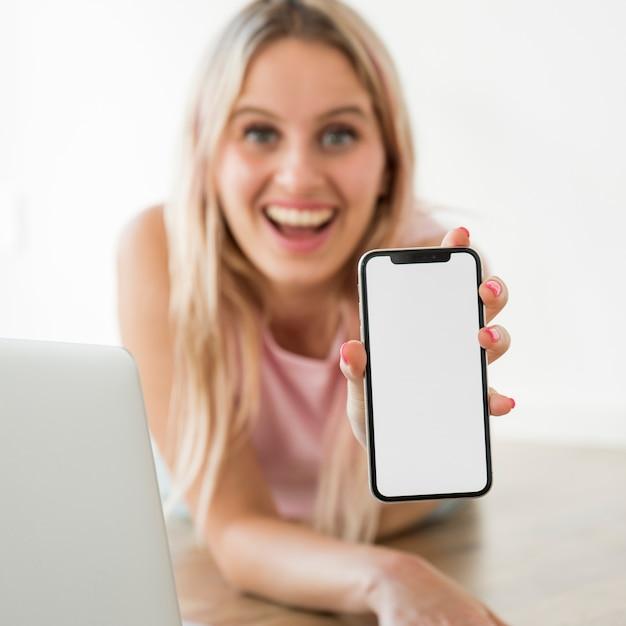 Influenciador loira mostrando smartphone no chão Foto gratuita