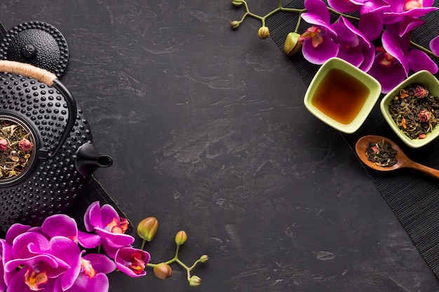 Ingrediente de chá de ervas e rosa flores frescas orquídea galho na superfície preta Foto gratuita
