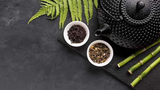Ingrediente de chá seco e vara de bambu com folhas de samambaia Foto gratuita