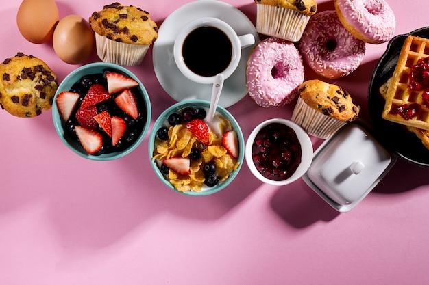 Ingredientes alimentares deliciosos e frescos do café da manhã no fundo brilhante cor-de-rosa. pronto para cozinhar. conceito de culinária saudável para casa. Foto gratuita