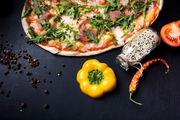 Ingredientes alimentares; especiarias e deliciosa pizza italiana em fundo preto de concreto Foto gratuita