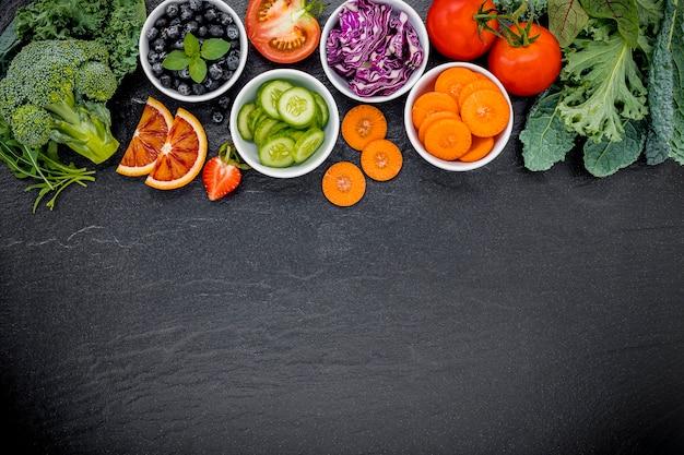 Ingredientes coloridos para saudáveis batidos e sucos no fundo escuro de pedra com espaço de cópia. Foto Premium
