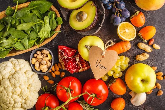 Ingredientes de comida vegan em um fundo escuro. legumes, frutas, cereais, nozes, feijão vista superior. Foto Premium
