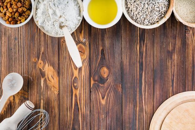 Ingredientes de cozimento na tigela sobre o fundo de madeira Foto gratuita