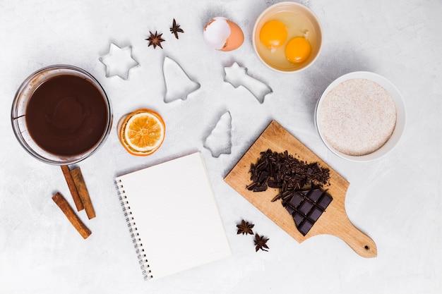 Ingredientes de fazer o bolo caseiro com cortadores de bloco de notas e pastelaria espiral sobre fundo branco Foto gratuita
