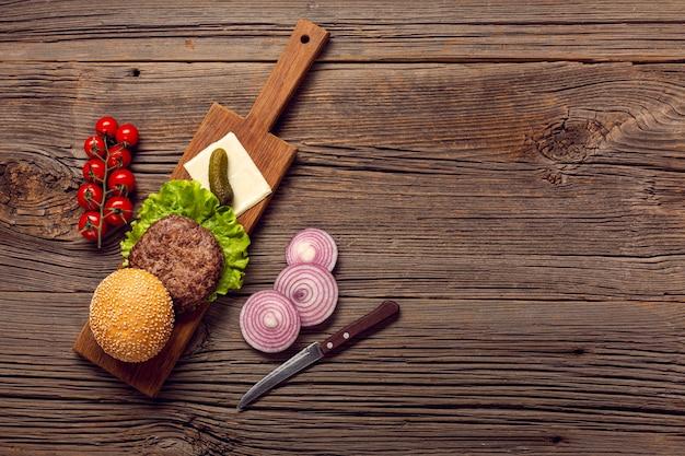 Ingredientes de hambúrguer de vista superior em uma placa de corte Foto gratuita