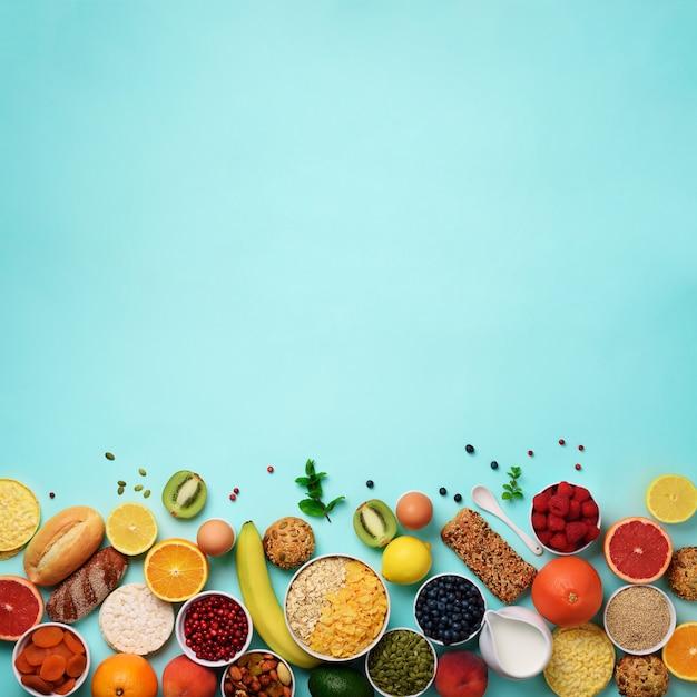 Ingredientes de pequeno-almoço saudável, quadro de comida. aveia e flocos de milho, ovos, nozes, frutas, frutas vermelhas, torradas, leite, iogurte, laranja, banana, pêssego Foto Premium