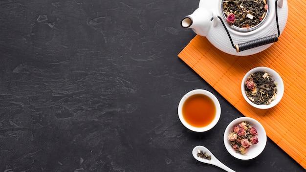 Ingredientes do chá seco na tigela de cerâmica com bule de chá em placemat sobre a superfície preta Foto gratuita