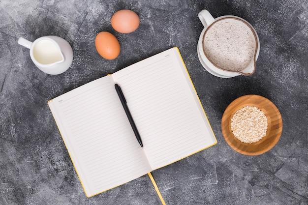 Ingredientes do pão com livro e caneta no pano de fundo concreto Foto gratuita