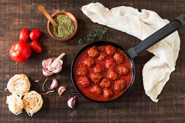Ingredientes e almôndegas com molho de tomate no fundo de madeira Foto gratuita