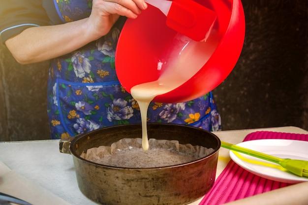 Ingredientes e utensílios de cozimento para cozinhar o bolo de esponja. processo de cozinhar pão de ló. mulher despeja a massa em uma assadeira Foto Premium