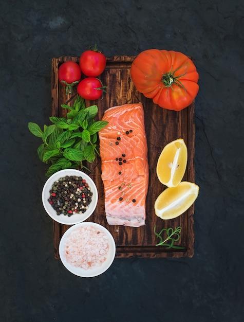 Ingredientes. filé de salmão cru, tomate cereja, limão e herança, hortelã fresca, especiarias na placa de madeira rústica sobre fundo de pedra escura Foto Premium