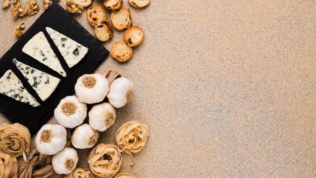 Ingredientes frescos e fatias de queijo gorgonzola na bandeja de ardósia sobre a superfície texturizada Foto gratuita