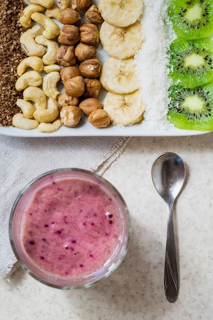 Ingredientes frescos para um café da manhã saudável alimentos crus e tigela de smoothie. kiwi, coco ralado, castanha de caju e avelã, tiro por cima, ingredientes para açaí Foto Premium