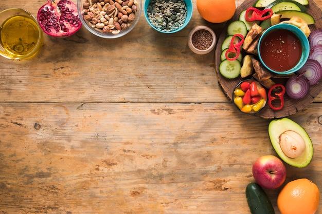 Ingredientes; frutas secas; frutas; óleo e legumes fatiados na mesa de madeira Foto gratuita