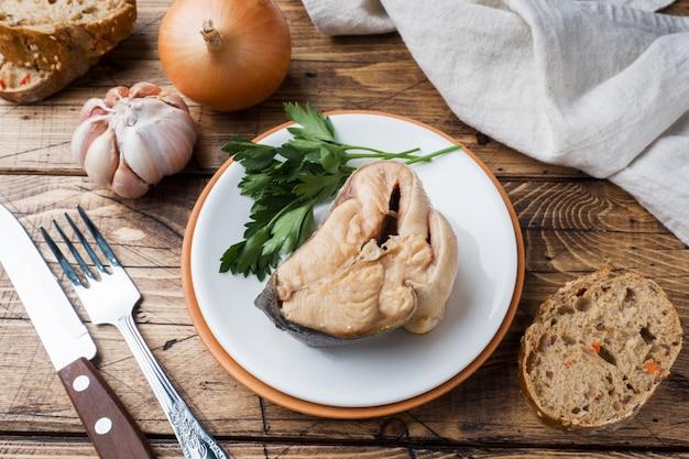 Ingredientes para a sopa salmon dos peixes, partes de pão, cebola e alho com verdes no fundo de madeira. Foto Premium