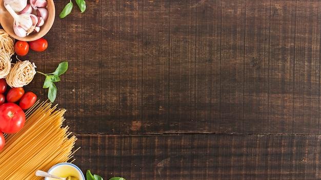 Ingredientes para cozinhar macarrão no fundo de madeira Foto gratuita