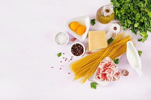 Ingredientes para cozinhar massas carbonara, espaguete com pancetta, ovo, pimentão, sal e queijo parmesão duro. Foto Premium