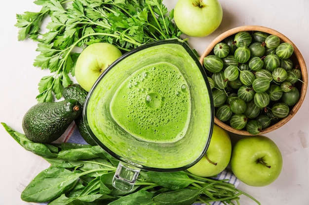 Ingredientes para fazer smoothies saudáveis de maçãs verdes, espinafre, abacate e salsa Foto Premium