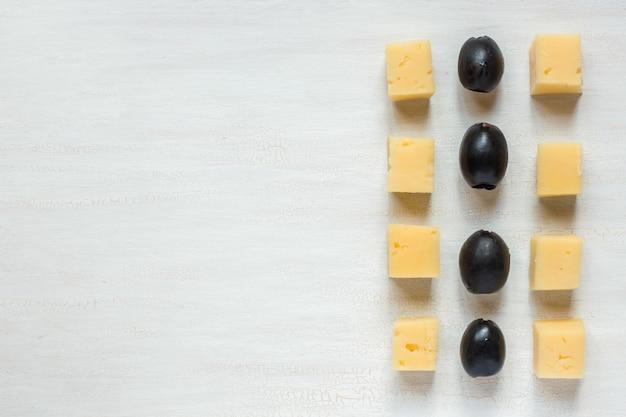 Ingredientes para lanches, queijo com azeitonas em uma mesa branca Foto Premium