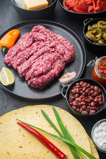 Ingredientes para quesadilla mexicana com molho de salsa, na mesa preta Foto Premium