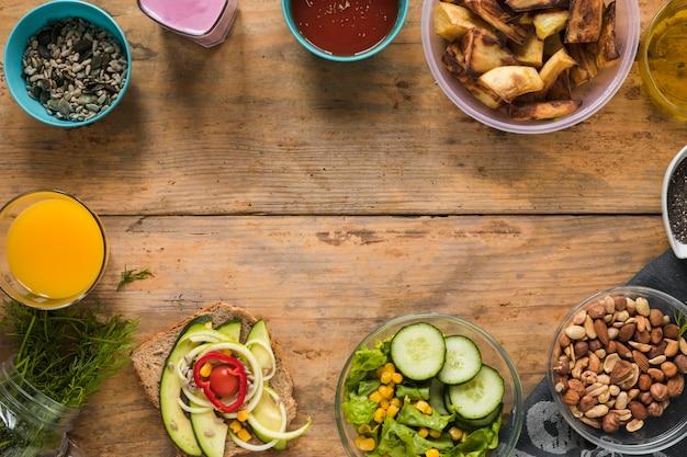 Ingredientes; suco; frutas secas; batata torrada; smoothie; sanduíche e óleo dispostos na mesa de madeira Foto gratuita
