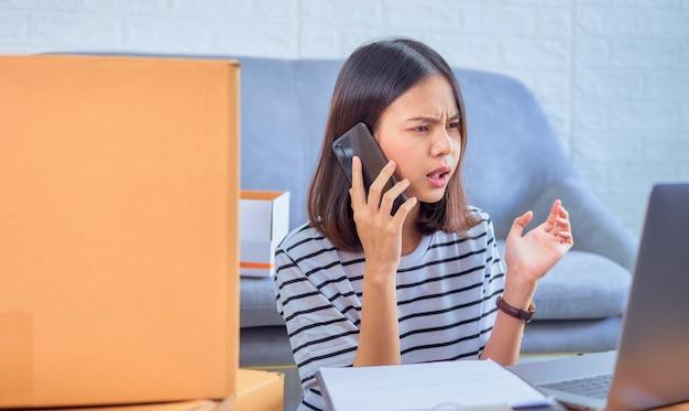 Inicialização de pequenas empresas, jovem mulher asiática, falando no smartphone com os clientes sobre como encomendar produtos, o vendedor prepara a caixa de entrega. Foto Premium