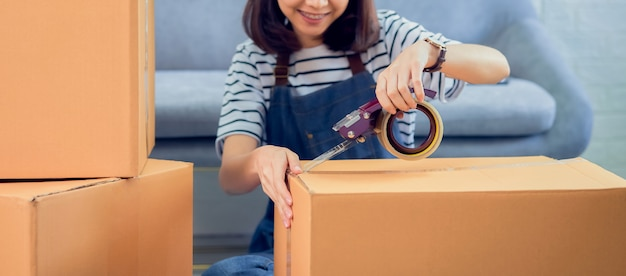 Inicialização de pequenas empresas, proprietário de jovem mulher asiática trabalhando e embalando na caixa para o cliente no sofá no escritório em casa, o vendedor prepara a entrega. Foto Premium