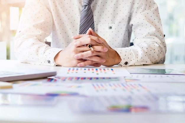 Início do processo de trabalho. empresário que trabalha na mesa de madeira com novo projeto de finanças. caderno moderno na mesa. caneta segurando a mão Foto gratuita